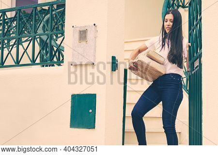 Latin Woman Taking Order And Closing External Gate. Thoughtful Young Female Customer Getting Express