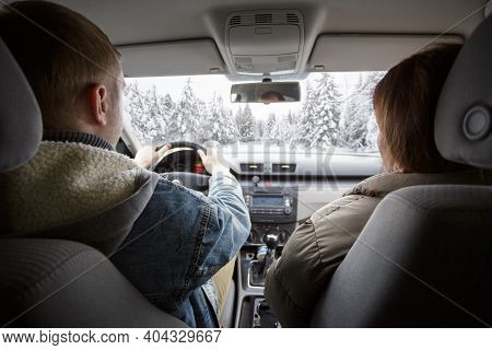 Back View Of Couple Enjoying Car Ride In Winter Forest
