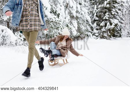 Man Pulling Sledge With Joyful Woman On Winter Day In Forest