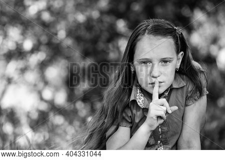 Girl with her finger over her mouth. Hushing. Black and white photo.