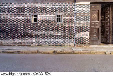 Wall With Black And Red Bricks With White Seam And Two Small Adjacent Windows With Metal Bars On Cob