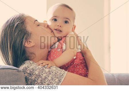 Caring Mother Sitting On Sofa And Kissing Her Little Daughter With Love. Adorable Baby Girl Looking