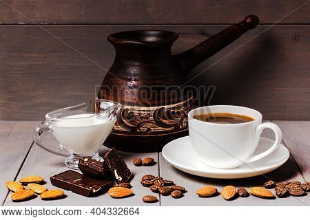 Still Life. On A Gray Table Is A Brown Ceramic Turk, A White Cup And Saucer Filled With Hot Black Co