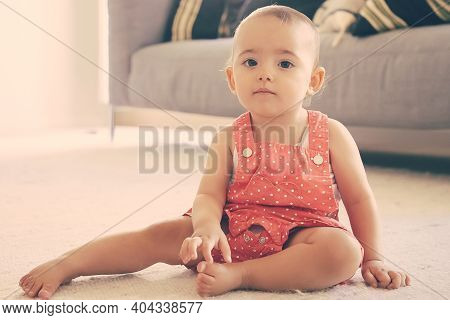 Serious Little Girl In Red Dungarees Shorts Sitting On Carpet At Home. Lovely Thoughtful Barefoot To