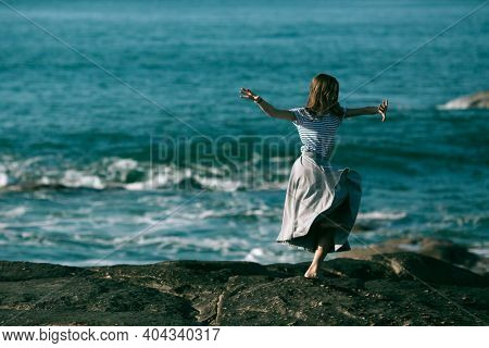 The dancers woman is engaged in choreography on the rocky coast of Atlantic ocean. Portugal.
