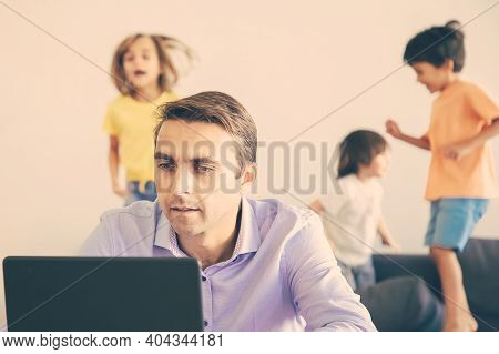 Serious Caucasian Dad Working Via Laptop And Kids Jumping On Background. Concentrated Father Using C