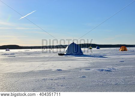 View Of Tents Camping On Ice Of The River During Ice Fishing. Fishermen On Frozen Lake Catch Fish In