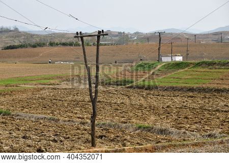 Countryside Landscape, North Korea. Plowed Fields And Power Line