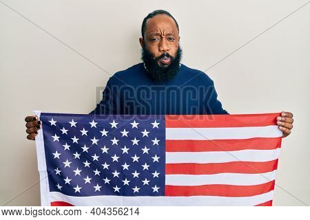 Young african american man holding united states flag puffing cheeks with funny face. mouth inflated with air, catching air.