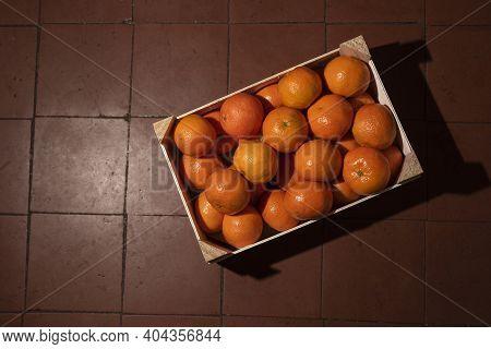 Tangerines (oranges, Clementines, Citrus) In Wooden Box On Garnet Tiles Background. Top View.