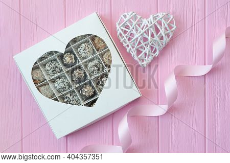 Chocolate Handmade Candies On Pink Wooden Table. Chocolate Box With Heart And A Festive Ribbon. Gift