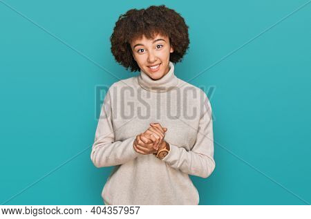 Young hispanic girl wearing wool winter sweater with hands together and crossed fingers smiling relaxed and cheerful. success and optimistic