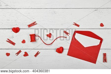 Preparing Valentine Gifts, Red Hearts, Twine, Clothespins And Note In Paper Envelope On White Wooden