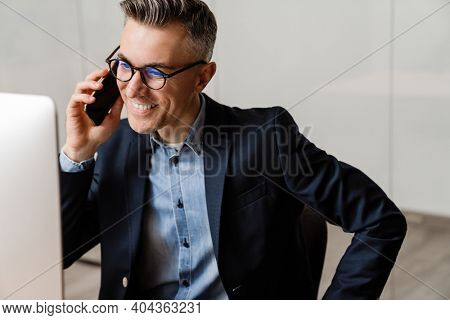 Smiling grey man talking on mobile phone while working with computer in office