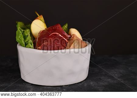 Dog Bowl Filled With Mixture Of Biologically Appropriate Raw Food Containing Meat Chunks, Fish, Frui