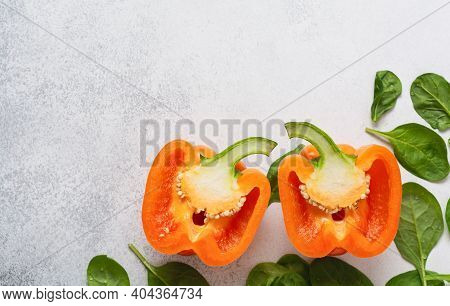 Orange Pepper Cut In Half And Fresh Spinach Leaves. Fresh Ingredients For Eating Vegetables, Spices,