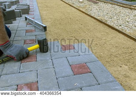 The Craftsman Installs And Lays Paving Stones On The Terrace, Road Or Sidewalk. A Worker Uses Stones