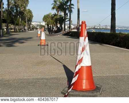 Limassol, Cyprus, January 20th, 2021: Red And White Striped Traffic Cones With A Barricade Tape To C