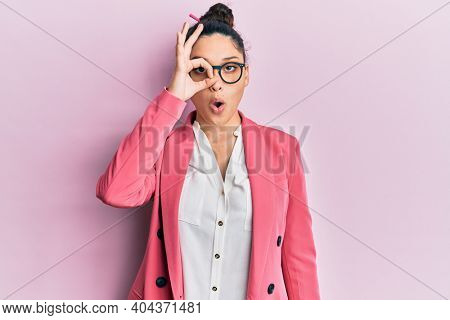 Beautiful middle eastern woman wearing business jacket and glasses doing ok gesture shocked with surprised face, eye looking through fingers. unbelieving expression.