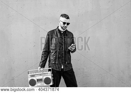Hipster Man Using Smartphone While Listening Music With A Vintage Boombox Player Against A Wall Back