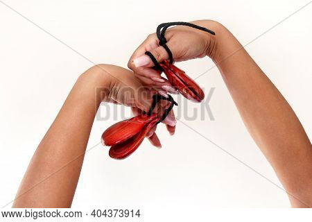 Spanish Castanets In The Hands On White Background, Close Up. Percussion Instrument Used In Flamenco