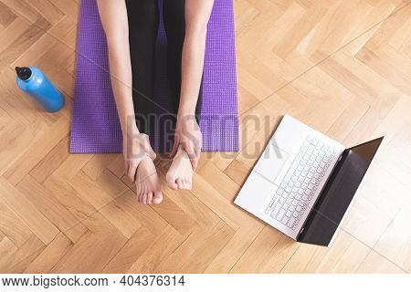 Young Happy Caucasian Woman, Stretching In The Living Room While Looking At Her Laptop. Health Care