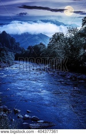 Mountain River Landscape In Summer. Wonderful Nature Scenery On Foggy Night. Clouds Rolling Over The