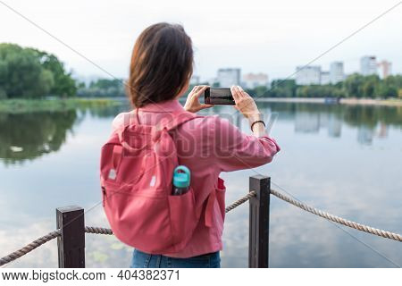Close-up, A View From Back, A Girl In Summer Pond Of River Lake, Records Video And Photos On A Smart
