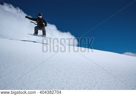 Woman Athlete Snowboarder In Flight After Jumping On A Snowy Slope Against A Background Of A Dark Bl