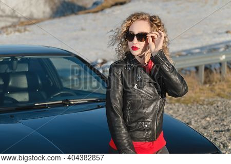 Attractive Blonde In Sunglasses And Leather Clothes Stands Near A Black Sports Car On A Country Road