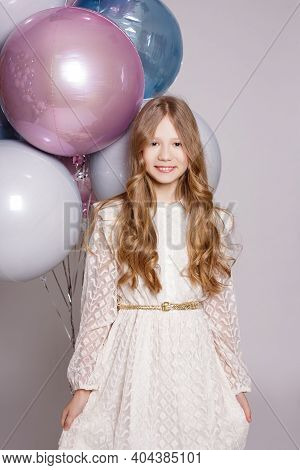 Childhood, Happiness And Birthday Party Concept - Happy Little Girl Posing With Pastel Air Balloons