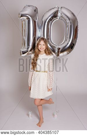 Birthday Concept - Happy Cute Girl With Number Ten Foil Helium Balloons Over White Background