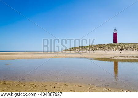 Lighthouse And Beach Of Texel With A Clear Blue Sky. Texel Is The Largest Wadden Island In The Nethe