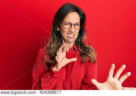 Young latin woman wearing casual clothes and glasses disgusted expression, displeased and fearful doing disgust face because aversion reaction. with hands raised