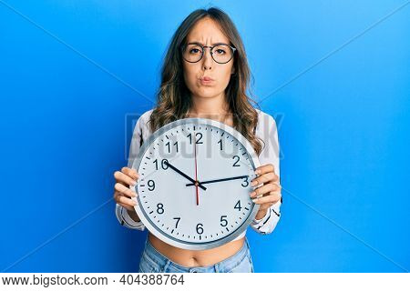 Young brunette woman holding big clock puffing cheeks with funny face. mouth inflated with air, catching air.