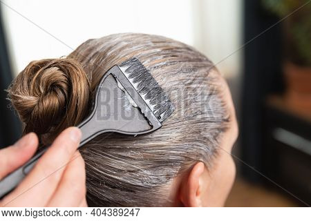 Hairdresser Applying Bleach Or Hair Color For Hair Dye With A Black Brush At Home Or Salon.