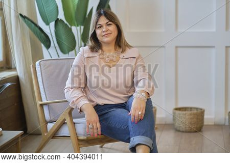 Attractive Middle Aged Woman Relaxing At Home. Smiling Woman Looking At Camera With Big Grin. Succes