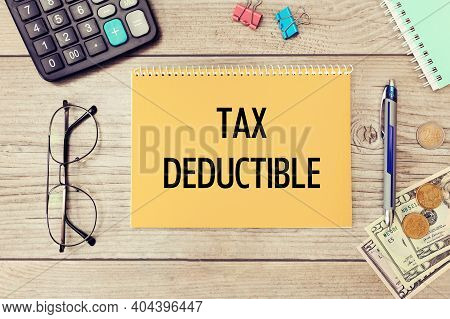 Notebook With The Text Tax Deduction On The Office Table Among The Stationery.