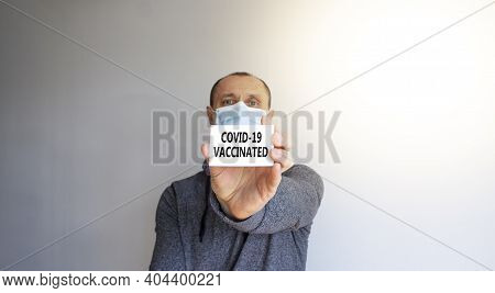 Covid-19 Vaccinated Symbol. White Card With Words 'covid-19 Vaccinated'. A Young Man In A Grey Wear