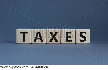 Taxes Symbol. Concept Word 'taxes' On Wooden Cubes On A Beautiful Grey Table. Grey Background. Busin