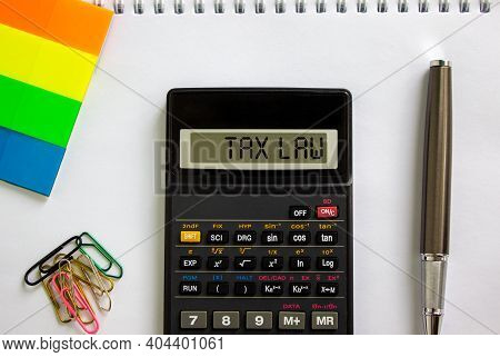 Tax Law Symbol. Calculator With Words 'tax Law', White Note, Colored Paper, Paper Clips, Pen. Beauti