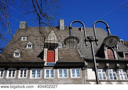 Goslar, Germany - April 21, 2016: Old medieval house in the historical center of Goslar. Roof and wall covered with natural black slate tiles.