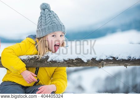 Funny Children Eat Snowflakes. Child Lick And Eating Snow In Winter. Children With Snow Flakes. Comi