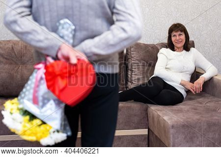 Happy Couple Seniors Celebrate Valentines Day. Man Holds Gift And Bouquet Of Flowers Behind His Back