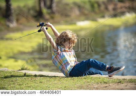 Boy With Fishing Rod At River. Little Fisher On The Lake. Kid At Jetty With Rod
