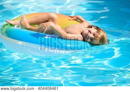 Child In Swimming Pool Playing In Water. Vacation And Traveling With Kids. Children Play Outdoors In