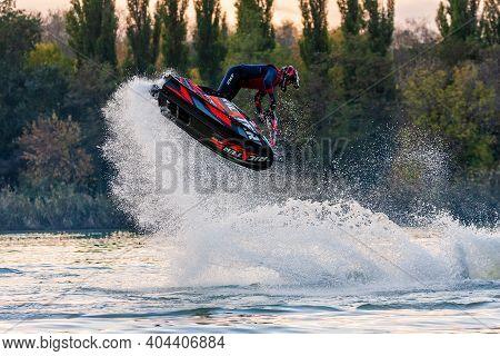 Krasnodar, Russia - October 25, 2020: Jet Ski Sportsman Doing Freestyle And Splashing In Evening Dur