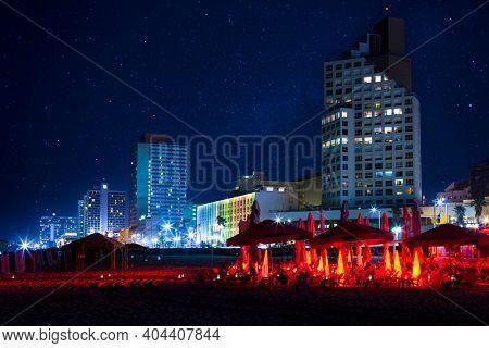 Tel Aviv Beach Under Starry Sky, Tel Aviv City At Night, City Lights Reflected On Water