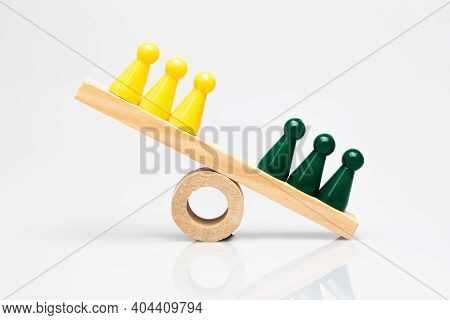 Green And Yellow Game Pieces On A Wooden Seesaw. Conceptual Shot Around Comparison, Competition Of T