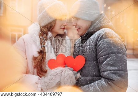 Young Loving Couple Outside On A Winter Day Holding Red Paper Hearts In Their Hands Feeling Joy And